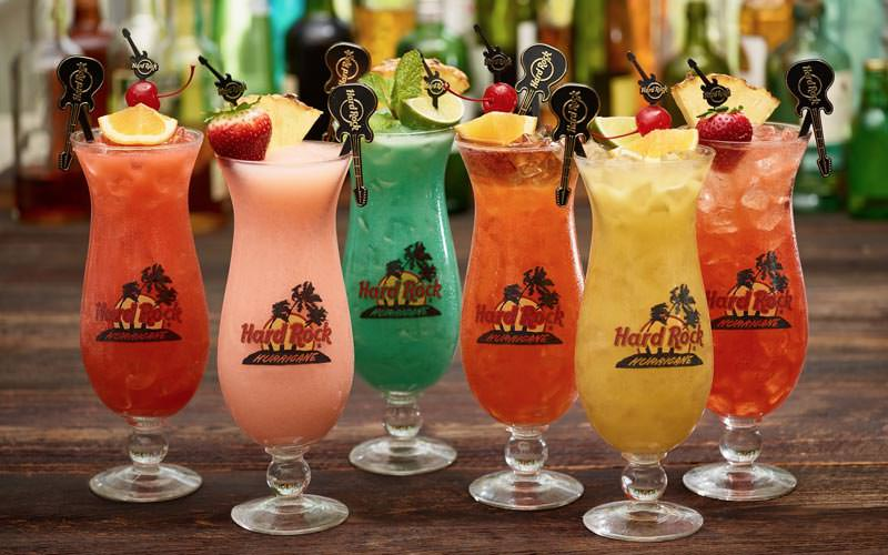 Image of six different coloured cocktails in tall cocktail glasses labelled with the hard rock cafe logo and with guitar shaped stirrers branded hard rock