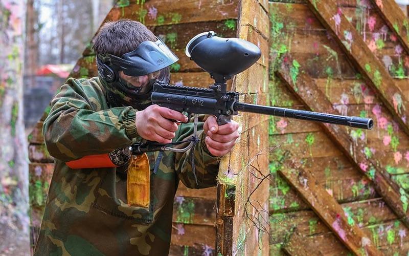 A man firing a paintball gun, with a peppered barricade behind him