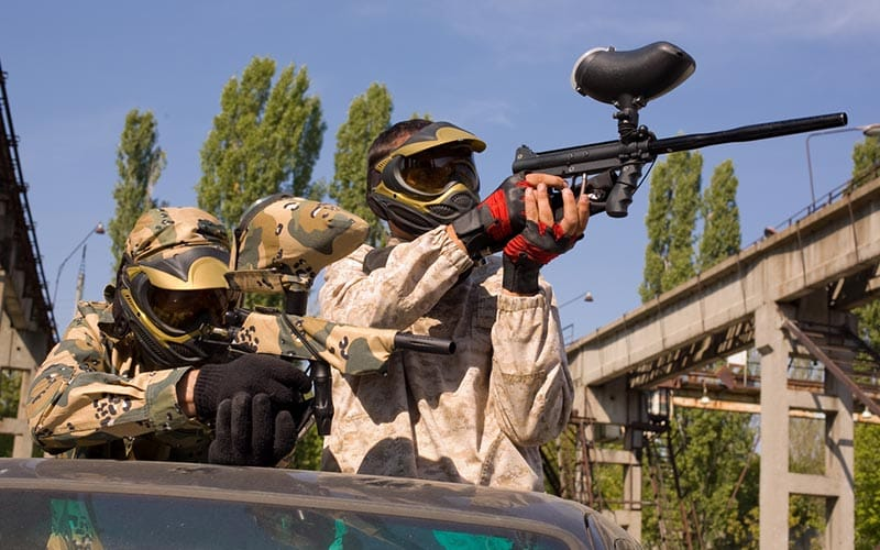 Some men in an open top jeep, one firing a paintball gun out of it