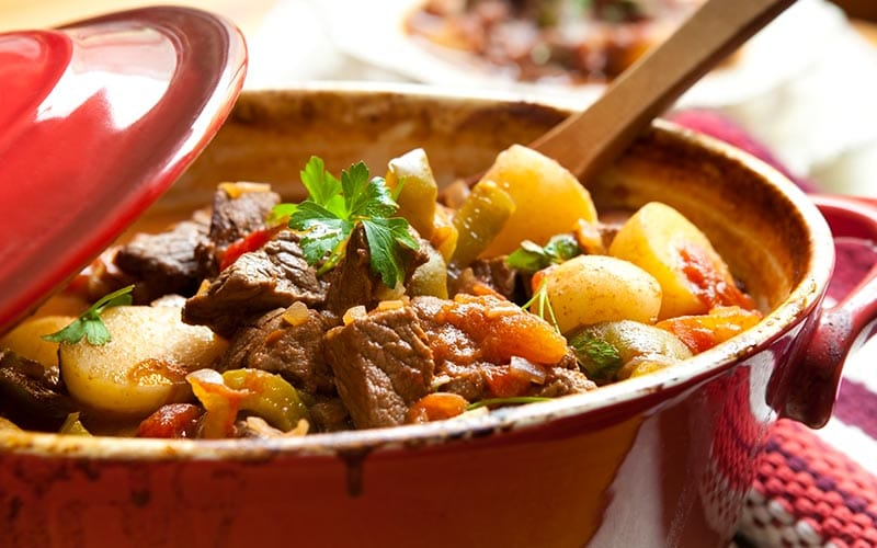 A pot of stew with a wooden spoon in