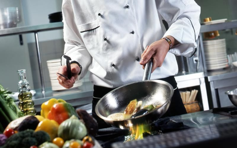 A chef cooking some food in a kitchen