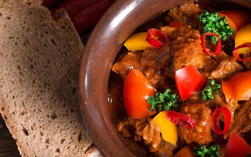 A bowl of stew with a piece of bread next to it