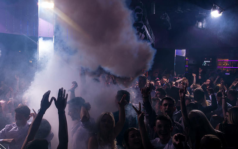 Men and women putting their hands up in the air in a club, to a backdrop of smoke