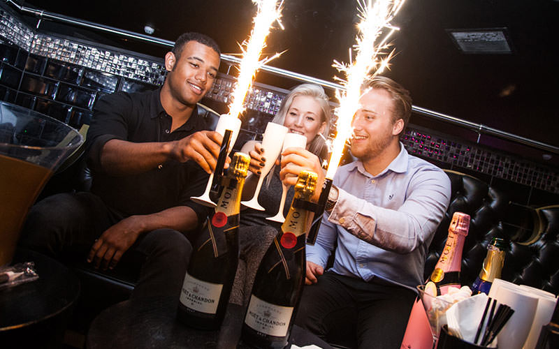 Three people toasting with two bottles of champagne in front, with sparklers coming out of the bottles