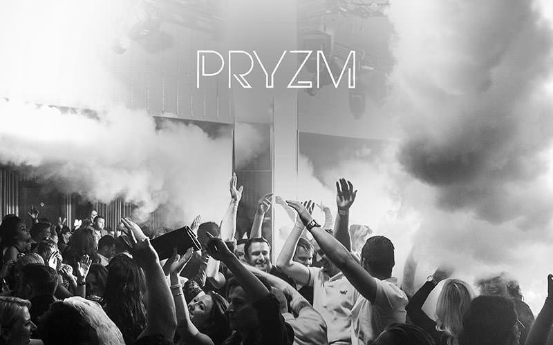 Pryzm logo on a black and white image of people dancing in the club to a backdrop of smoke