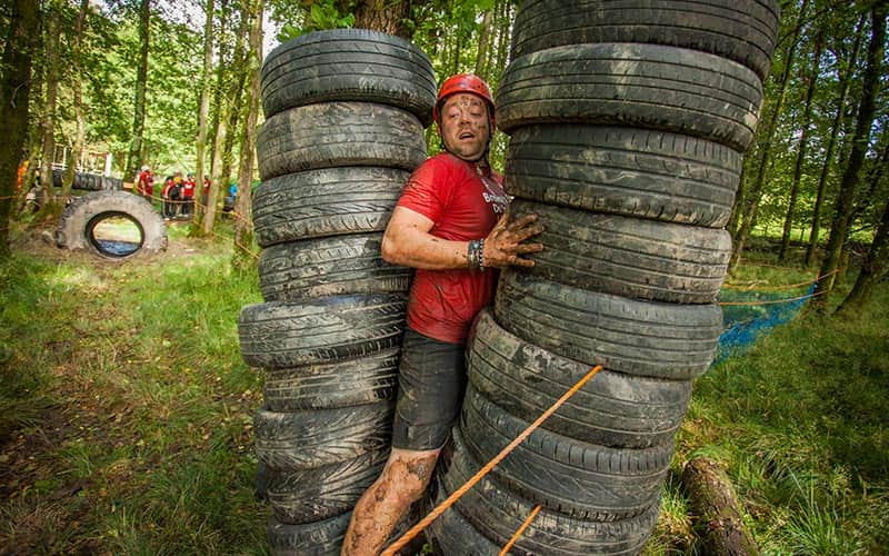 A man squeezing through two tyre towers