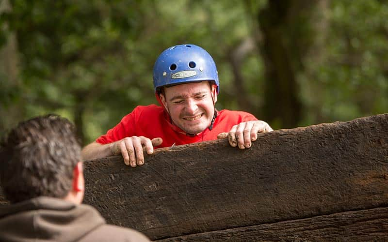A man climbing over a wooden fence with a man looking on in the foreground