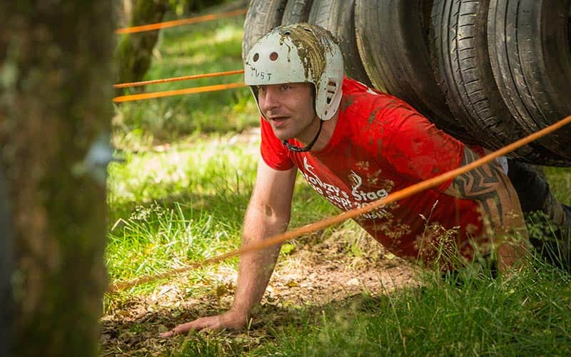 A man climbing out from under tyres in a forest