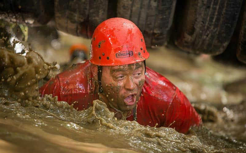A man climbing out from under tyres in a mud river