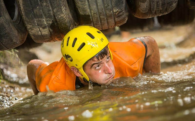 A man climbing out from under tyres in a muddy river