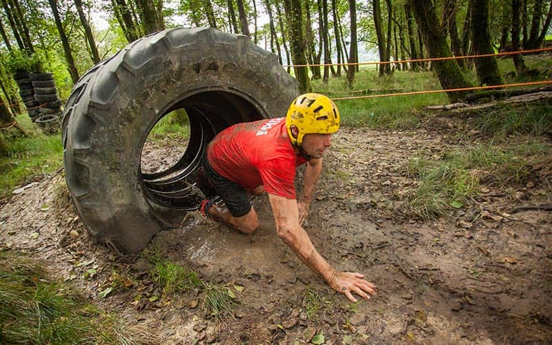 A man walking out of a tyre onto mud
