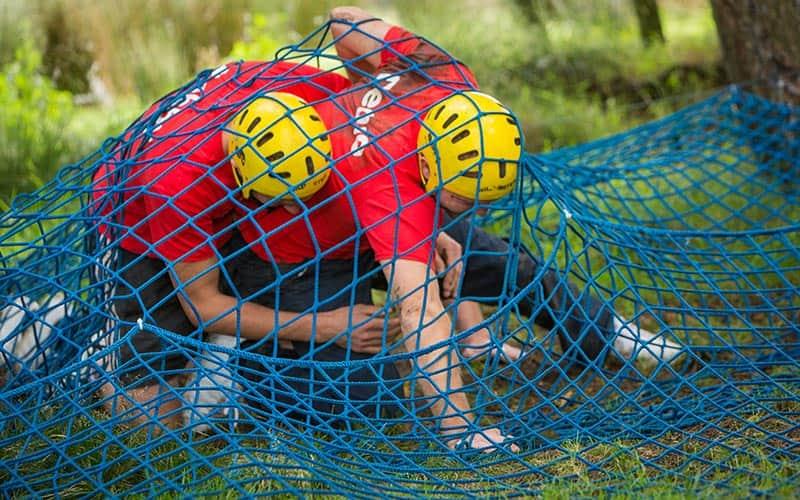 Two men walking under a net in the forest