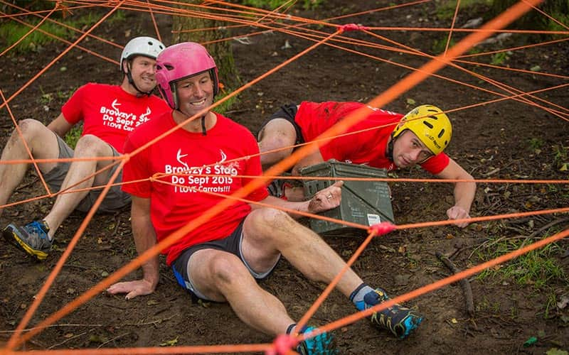 Three men walking under ropes on mud