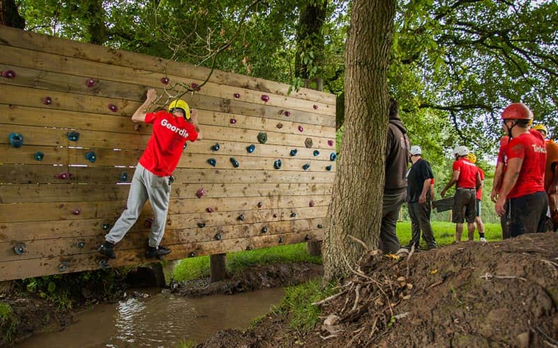 A man on a climbing wall over a muddy river, with others looking on in the background