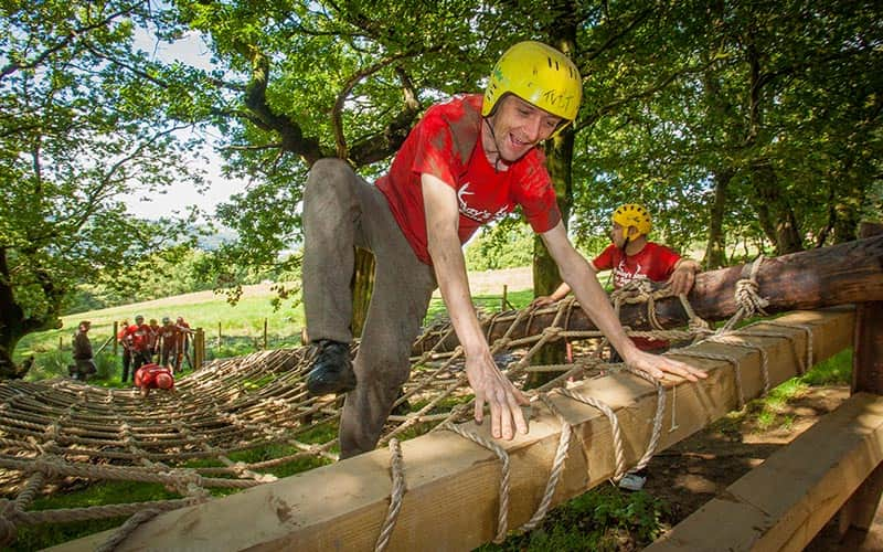 A man climbing off a rope ladder and over a wooden block in a forest, with others in the background