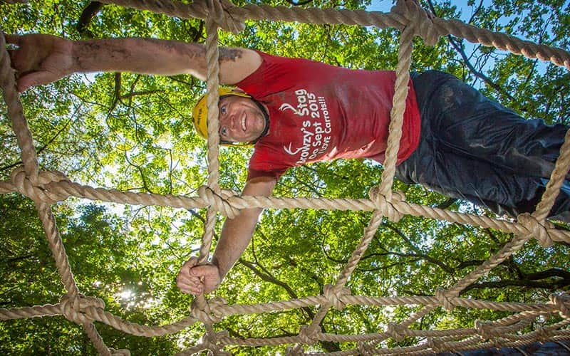 A camera looking up at a man climbing a rope ladder in the forest