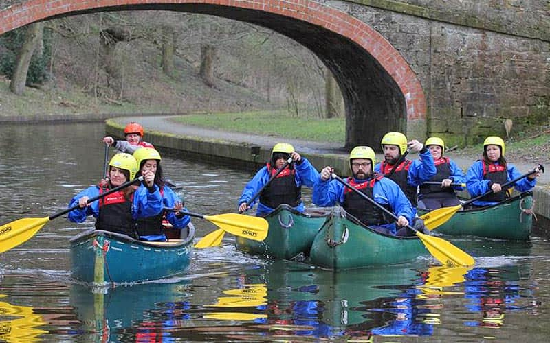 Some people in kayaks travelling down a river under a bridge