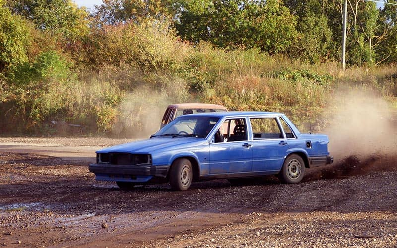 Two cars racing around a dirt field