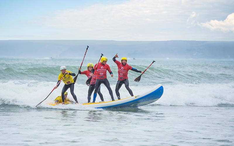 Four people stood on a SUP board and riding the waves