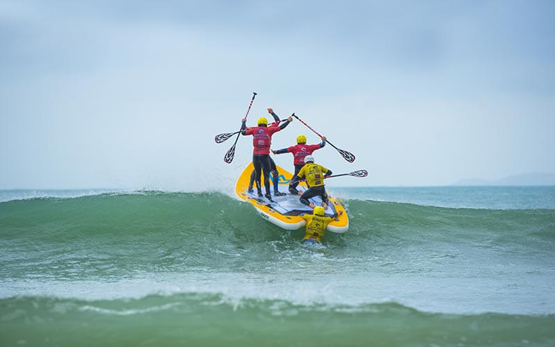 Three people stood on a SUP board and riding a wave, with a person hanging onto the back
