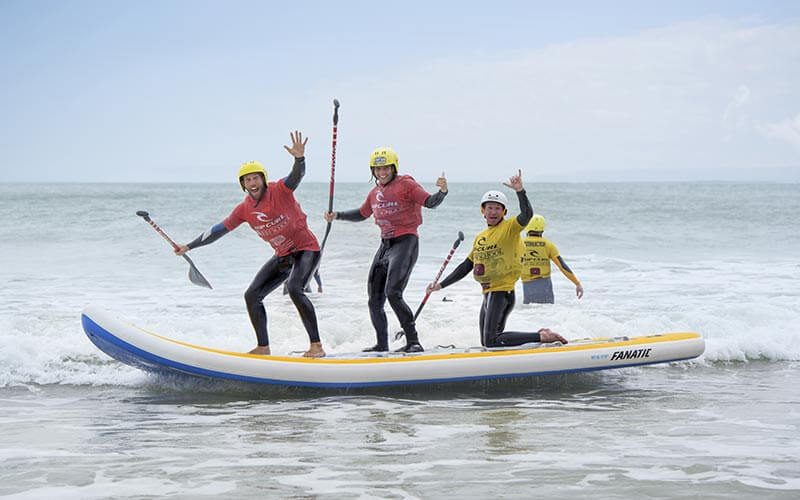 Three people holding their hands in the air whilst stood on a SUP board in the sea