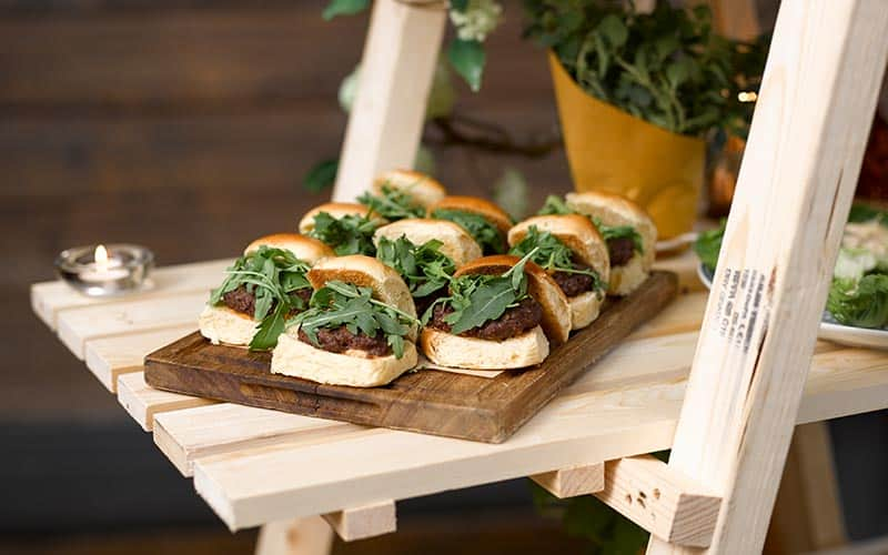 Wooden platter of burger sliders, served on a makeshift ladder