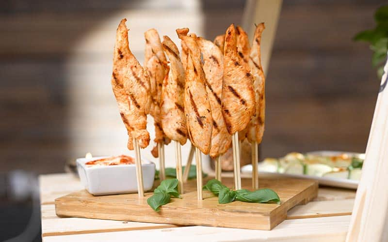 Chicken skewers with dip, in a wooden board