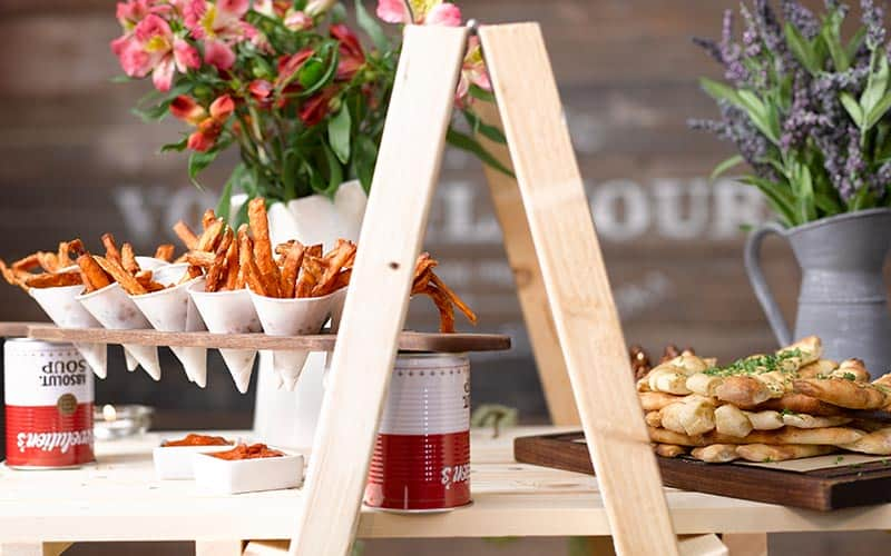 Close up of food served up on a makeshift wooden ladder, with plants in the background
