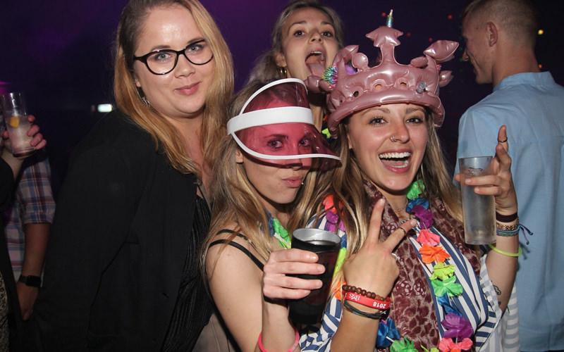 A group of women in a nightclub wearing novelty headwear