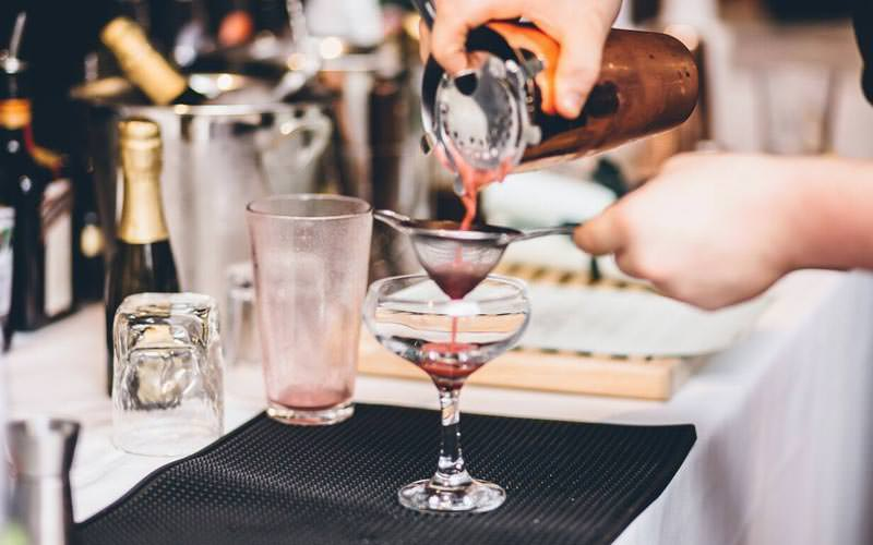 Image of a cocktail being poured from a cocktail shaker through a strainer and into a glass at the bar