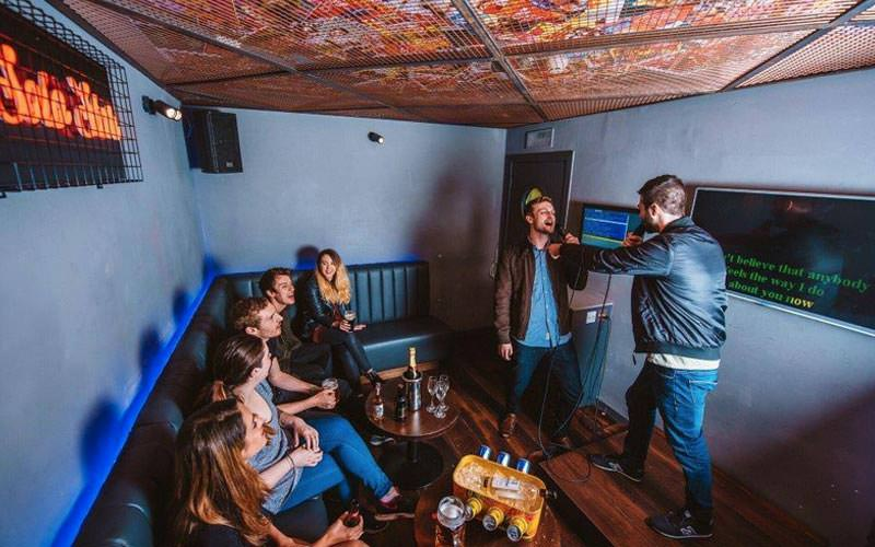 Image of a group of people sitting down in a room while two men are singing karaoke with the lyrics showing on a wide screen tv built into the wall
