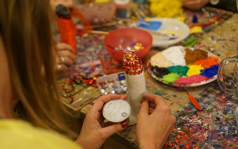 Close up image of a girl sticking sequins onto a dildo