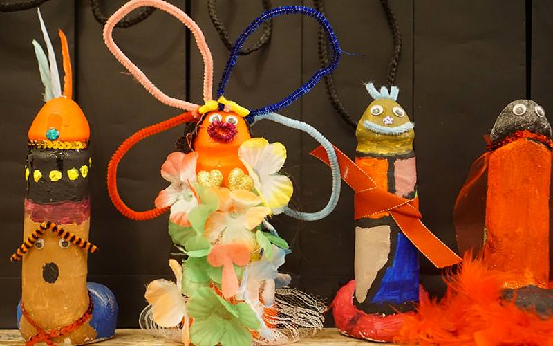 Image of four dildos that have been decorated with paints and accessories