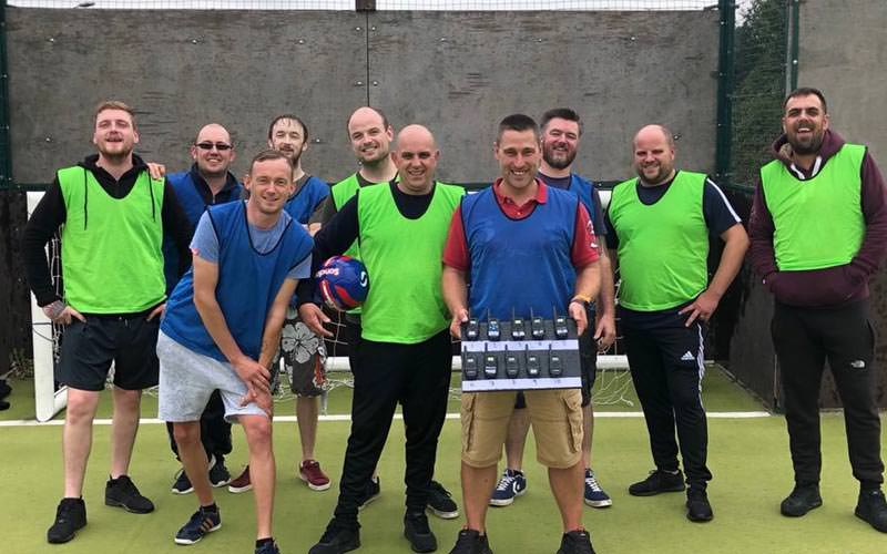 Image of a group on a 4g pitch wearing green and blue bibs and one guy holding a box filled with buzzers