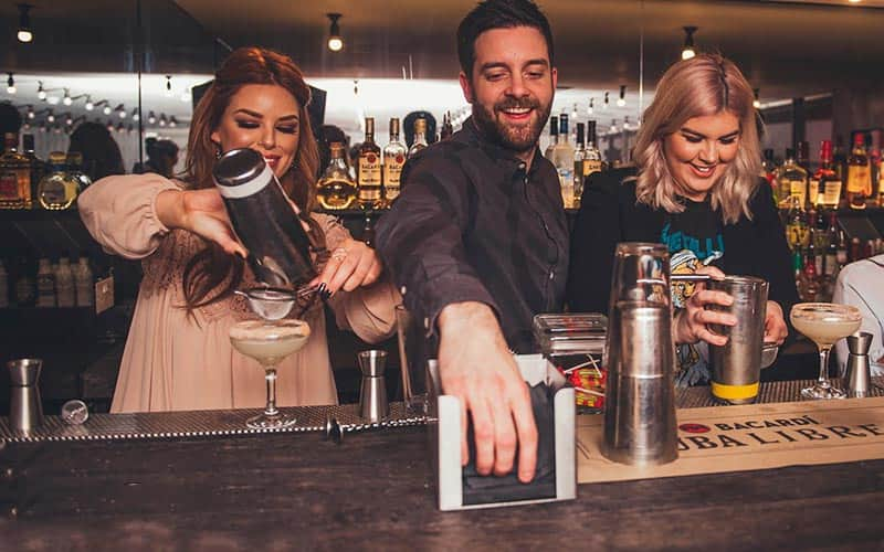 A barman helping two girls make cocktails in a cocktail class