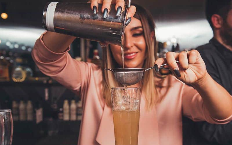 A girl pouring a cocktail from a cocktail shaker into a glass, through a sieve