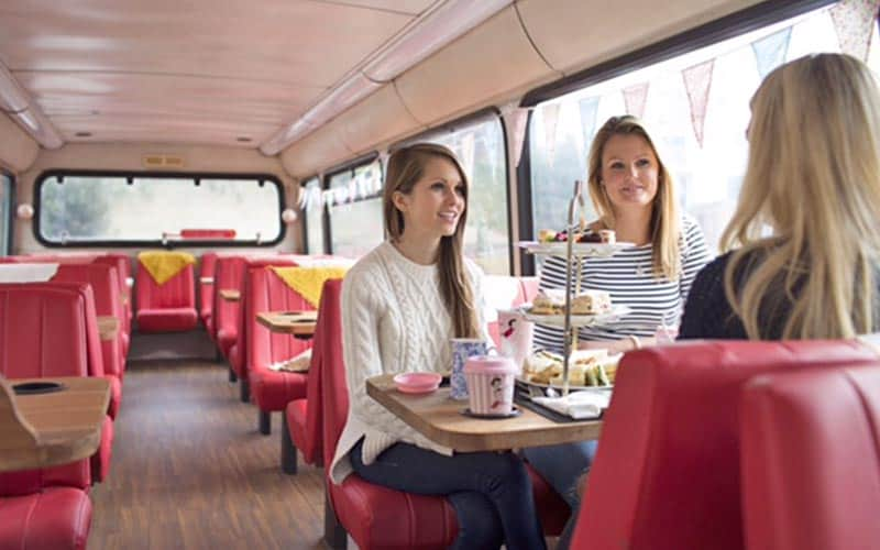Three girls having an afternoon tea on a bus