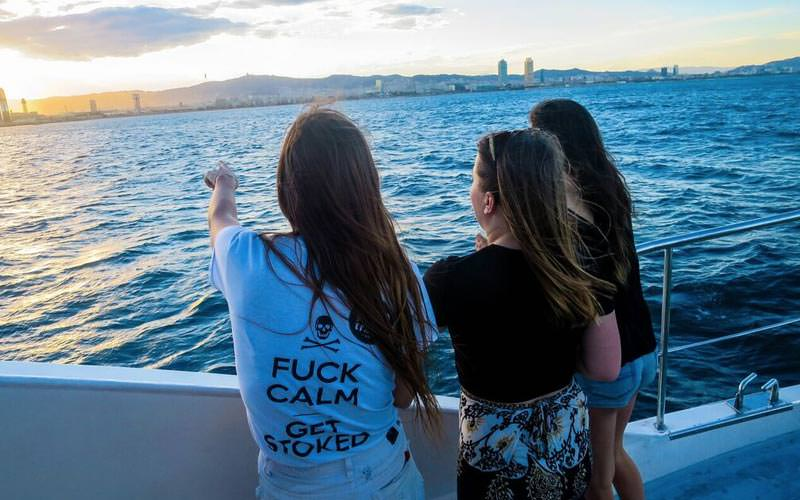 Image of three girls on a catamaran in barcelona pointing to the water