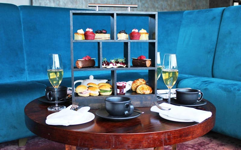 Image of a table set with a wooden style box with compartments filled with sandwiches and cakes and scones with two glasses of champayne on the table