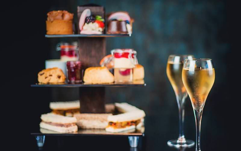 Image of a three tiered wooden style stand filled with sandwiches and scones and cakes with two glasses of champayne