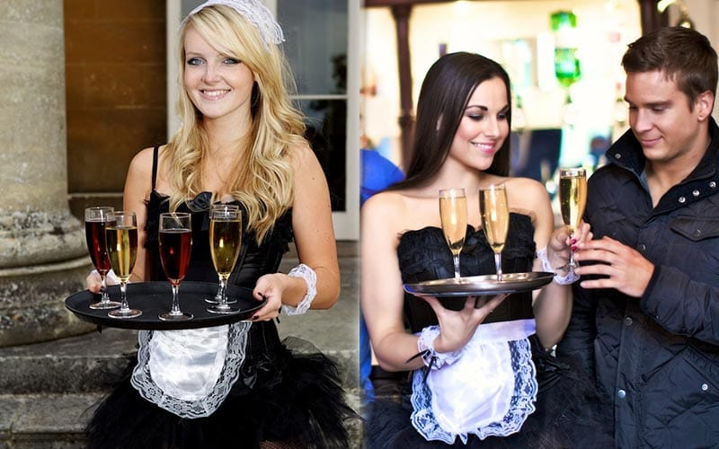 Two butlerettes carrying drinks on trays, with one stag party getting a drink off one.