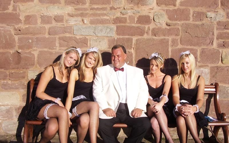 Man in white tux jacket and bow tie, sitting on bench with two butlerettes on either side.