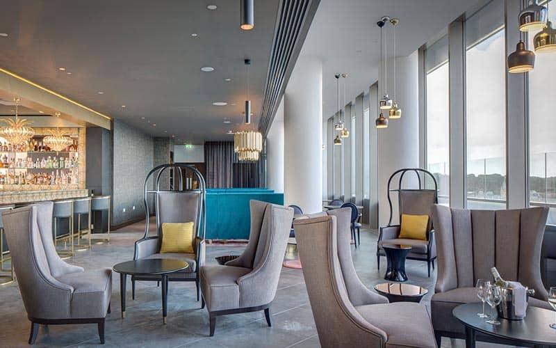 Plush grey chairs in Level8 Sky Bar