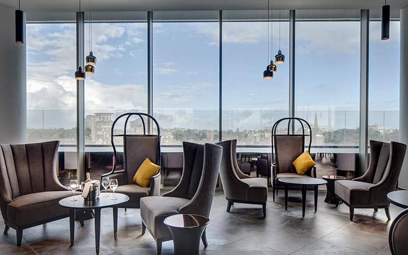 Tables and chairs in Level8 Sky Bar, with a backdrop of a panoramic skyline