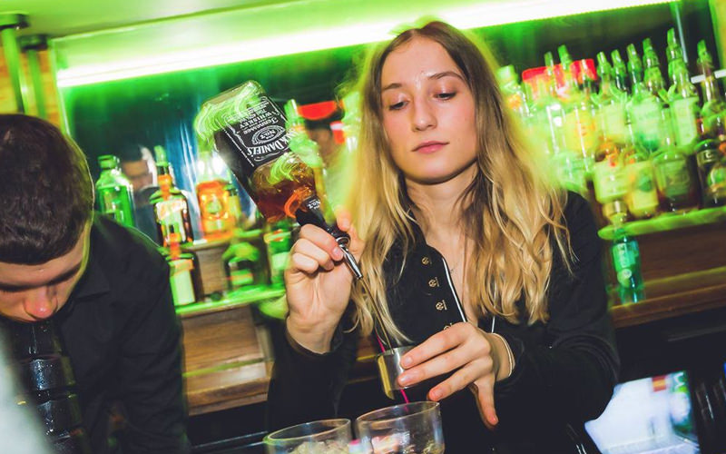 A woman pouring whisky into a measuring glass