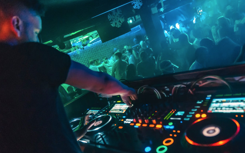 A DJ in front of a crowd in a club