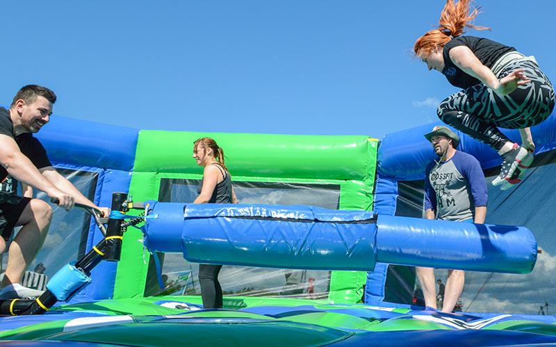 A man on a bike pedalling and turning a foam arm as people jump to avoid it, within the large inflatable.