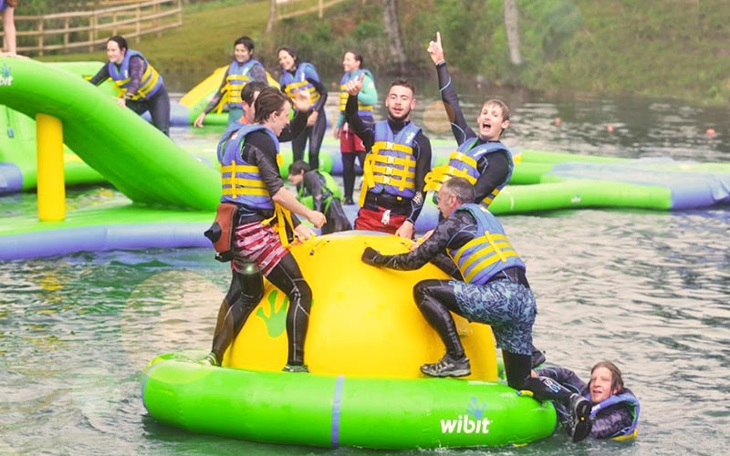 Groups of people stood on inflatable objects in the water
