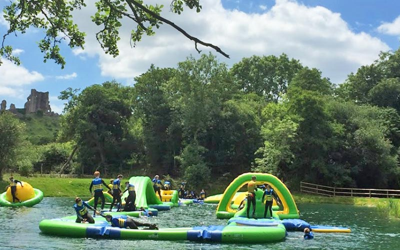 People stood on inflatable objects in the water