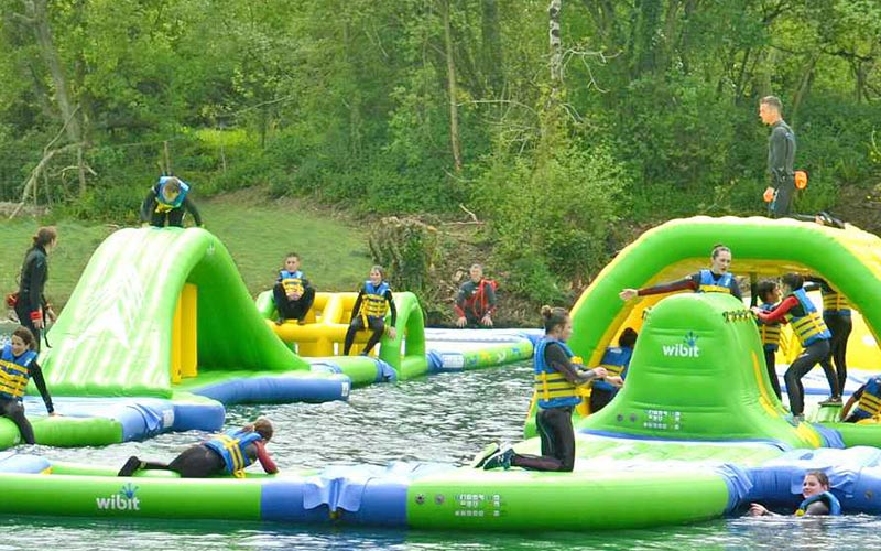 People climbing inflatable objects in the water